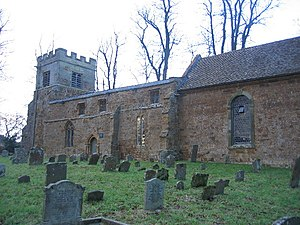 Part of a stone church seen from an angle.  At the far end is a battlemented tower, in front of which is a nave with a flat parapet, and part of a chancel with a tiled roof