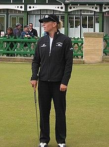 Golfeuse, debout, avec une casquette, et tenant un club dans la main droite.