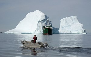 Royal Arctic Line - The supply ship Vestlandia approaches Upernavik in front of an iceberg.
