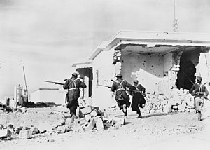 Soldiers wearing greatcoats and steel helmets with fixed bayonets run past whitewashed buildings damaged by shellfire.