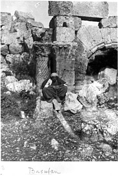 Basufan Church of St. Phocas - Apse and arch of Prothesis - Corinthian columns with spiral fluting and wind blown capital. Kurdish man seated in foreground.jpg