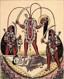 A decapitated, nude, red-complexioned goddess stands on a copulating couple inside a large lotus. She holds her severed head and a scimitar. Three streams of blood from her neck feed her head and two nude, red-coloured women holding a scimitar and a male severed head, who flank her. All three wears a garland of severed heads, a serpent (around her neck) and various gold and pearl jewellery.