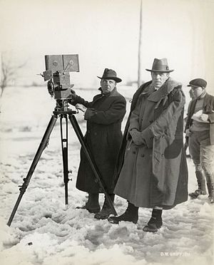 """Billy Bitzer - Cameraman G. W. """"Billy"""" Bitzer and director D. W. Griffith on location in the snow filming Way Down East (Griffith, 1920). Bitzer stands behind a Pathé camera."""