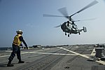 Boatswain's Mate 3rd Class directs INS Ranvijay's KV-28 Helix helicopter as it prepares to land on the flight deck of USS McCampbell (DDG 85).jpg