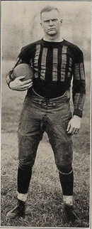 An unsmiling Bomar, holding a football