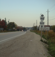 A two-lane undivided road in a rural area with a reassurance marker for Ontario Highway 48 north pointing straight