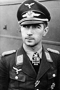 The head and shoulders of a young man. He wears a uniform and peaked cap, with an Iron Cross displayed at the front of his shirt collar.