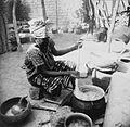 COLLECTIE TROPENMUSEUM Een Samo vrouw bezig met het roeren in een pot met sorghum of gierstepap TMnr 20010245.jpg