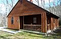 Cabin 16 allows six, sleeps six. This two-bedroom cinderblock with cedar siding cabin has two sets of bunk beds and one queen bed. Central heat and air and linens are included.Cabins with a similar (25736778741).jpg