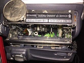 DV - Mini-DV tape mechanism inside an early 2000s Panasonic Palmcorder. Quarter for scale.