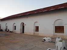 The white facade of a single-storey building, extending away from the viewer to the left. There is a single arched doorway, and a row of windows set into arched recesses. The roof is rusty corrugated metal. Four low white posts are linked by chains in the right foreground, one of them has been knocked over. Two ladies are visible in front of the left-most window. One sits on a dark plastic chair looking into a pram, the other stands behind the pram, also looking at it.
