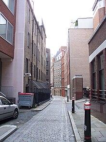 La photo montre une allée pavée de pierres taillées et qui est entourée d'immeubles.