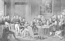 Gravure en nuances de gris, présentant une assemblée d'hommes, en uniformes couverts de décorations, dans une large pièce décorée d'un tableau et d'un buste. Certains, au centre et à droite, sont assis autour d'une table ronde ornée d'une nappe et sur laquelle plusieurs papiers sont posés. Parmi ceux assis au premier plan, cinq personnages : deux à droite, deux au centre, un à gauche. Deux autres sont assis au second plan, derrière la table. De nombreux autres sont debout, à gauche et au second plan.