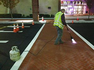 Decorative concrete - Construction of a polymer cement overlay to change asphalt pavement to brick texture and color to create decorative crosswalk and traffic calming in high-pedestrian area.