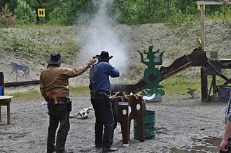 Cowboy action shooting - A CAS shooter engages a target with his lever-action rifle. To the left, the range officer with a timer that measures the shooter's stage time.