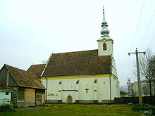 A small church with a tower and a nearby small wooden building
