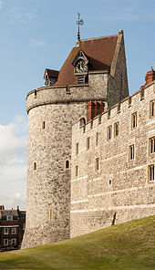 A photograph of a castle tower, the tower is pierced by small windows and has a coned, red-tiled roof, with a clock built into one side. The sky behind the wall is pale blue.