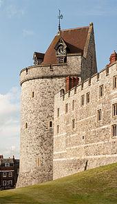 Ein Foto eines Burgturms, der Turm ist von kleinen Fenstern durchbrochen und hat ein kegeliges, rotes Ziegeldach, in dessen eine Seite eine Uhr eingebaut ist.  Der Himmel hinter der Mauer ist hellblau.