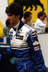 Damon Hill in racing uniform walking to the right