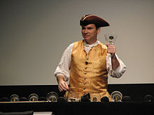 Man wearing tricorn hat and vest ringing a glass handbell