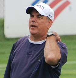 Candid photograph of Pees wearing a blue t-shirt and white baseball cap bearing the New England Patriots logo on a football field