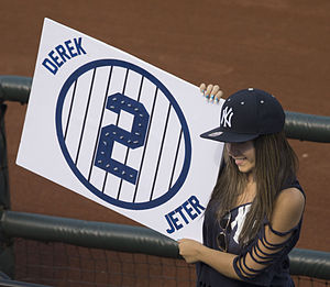 """A woman with brown hair wearing a navy blue hat and navy blue shirt holds a sign to her right with the word """"DEREK"""" at the top left, the word """"JETER"""" at the bottom right, and a navy blue circle with navy blue vertical stripes and the number 2 inside it in the center."""