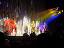 Three woman are shown to be performing; multi-colored lights shine upon them