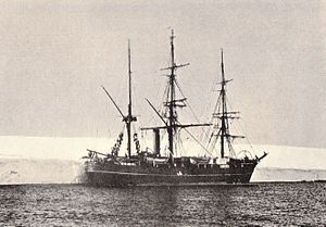 Three-masted ship with sails furled, lying next to a shelf of ice.