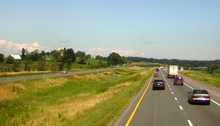 A four lane divided highway among short hills travels into the background and curves to the right. The two divided halves are separated by a depressed swampy median.