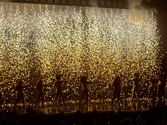 """The Mrs. Carter Show World Tour - Beyoncé performing """"End of Time"""" with the French dancing duo Les Twins and her background dancers as pyrotechnics fall on stage"""