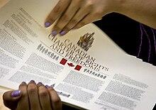 Image d'un poster intitulé «Canadian Charter of Rights and Freedoms» tenue par deux mains.