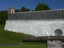 A historic fort, with a wooden fence over a white stone wall that encircles the fort.Fort Mackinac in 2004