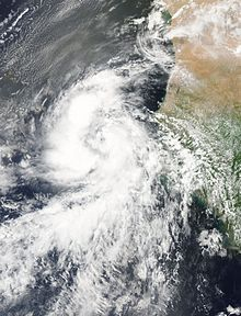 A satellite image shows Fred as a tropical storm, situated right between the Cape Verde Islands and the coast of West Africa. The storm is supporting thick thunderstorm clouds, arranged in two prominent bands.
