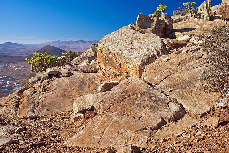 "File:Fuerteventura, mount Tindaya, ancient ""graffiti"" in crude shape of footprints, ""podomorphs"" and opuntia.jpg"