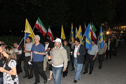 MEK demonstrators carrying Lion and Sun flags and those of 'National Liberation Army of Iran' Gathering 3.jpg