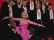 Marilyn Monroe in a pink gown, surrounded by men in tuxedos