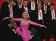 Monroe w Gentlemen Prefer Blondes.  Ma na sobie szokującą różową sukienkę z dopasowanymi rękawiczkami i diamentową biżuterią i jest otoczona przez mężczyzn w smokingach