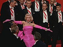 Monroe in Gentlemen Prefer Blondes. She is wearing a shocking pink dress with matching gloves and diamond jewelry, and is surrounded by men in tuxedos