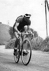 Photographie en noir et blanc d'un cycliste courbé sur son vélo, pédalant dans la montée d'un col.