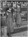 Girls operate stock boards at Waldorf-Astoria. The Waldorf-Astoria Hotel is employing girls to operate tickers and... - NARA - 533759.tif