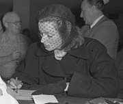 A veiled Garbo in dark coat and hat writes at a counter.