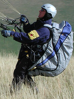 Paragliding - A pilot with harness (light blue), performing a reverse launch