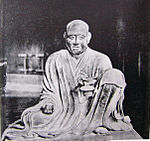 Gyōga. Frontal view of a seated monk with the left leg propped up.