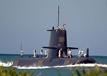 A submarine with people wearing white uniforms standing on the outer hull