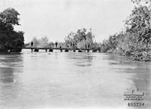 7 soldiers standing on pontoon bridge in middle distance; fast flowing wide River Jordan in foreground; lush growth on both banks.