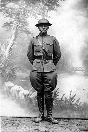 Truman in military uniform with shoulder and waist belt with helmet