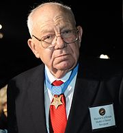 Head and shoulders of a gray-haired white man wearing glasses, a suit and tie, and a star-shaped medal hanging from a blue ribbon around his neck.