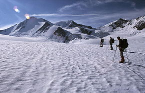 Three mountaineers on a snow-covered icefield with mountain peaks in the distance