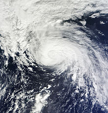 Satellite image of an organized with a ragged eye and some spread out mass of clouds.