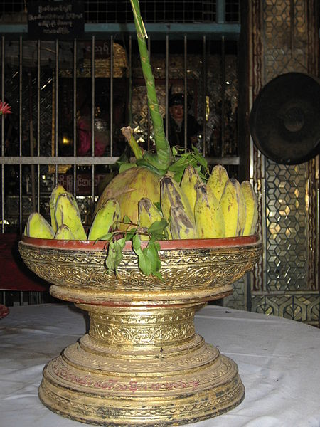 Traditional offerings of bananas and coconut at a Nat spirit shrine in Myanmar